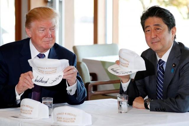 """Tổng thống Trump và Thủ tướng Abe cùng ký tên vào những chiếc mũ màu trắng với khẩu hiệu """"Donald và Shinzo làm cho liên minh vĩ đại hơn""""."""