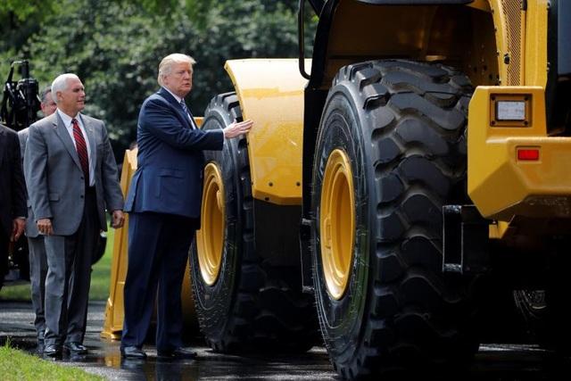 """Phát biểu trước các lãnh đạo doanh nghiệp, Tổng thống Trump nói: """"Tôi muốn cam kết với từng người trong số các bạn rằng: chúng ta sẽ không cho phép các nước khác phá vỡ luật lệ, ăn cắp việc làm và bòn rút sự giàu có của chúng ta"""". Trong ảnh: Tổng thống Trump và Phó Tổng thống Pence đứng cạnh một sản phẩm do doanh nghiệp Mỹ sản xuất và mang tới trưng bày tại khuôn viên Nhà Trắng."""