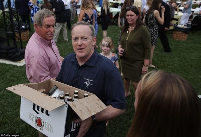 Thư ký Báo chí Nhà Trắng Sean Spicer (thứ hai từ trái sang) ôm thùng bia và rượu cho các thành viên trong đội ngũ truyền thông của Nhà Trắng tại sự kiện ở bãi cỏ phía nam. (Ảnh: Getty)