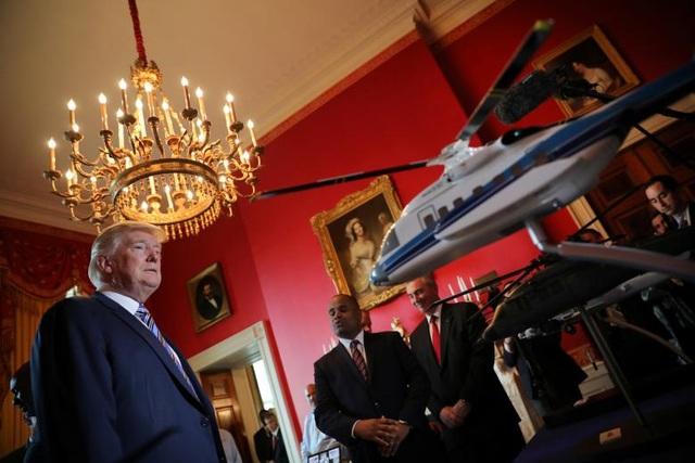 """Từ khi còn là ứng viên tranh cử tổng thống, ông Trump đã đề cao chính sách """"Nước Mỹ là số một"""" và mong muốn các doanh nghiệp Mỹ sẽ phát triển mạnh hơn tại thị trường nội địa. Trong ảnh: Tổng thống Trump quan sát mô hình thu nhỏ của mẫu trực thăng Sikorsky được trưng bày tại triển lãm."""