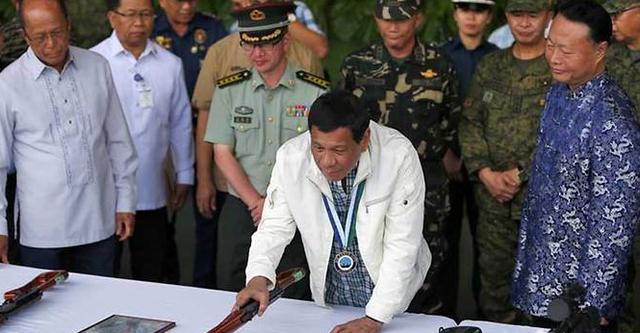 Tổng thống Rodrigo Duterte (áo trắng) kiểm tra số vũ khí do Trung Quốc trao tặng. Đứng cạnh ông là Đại sứ Trung Quốc tại Philippines Triệu Giám Hoa (phải) (Ảnh: AFP)