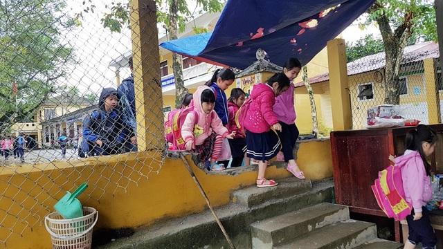 Các học sinh đi xuyên tường qua một lỗ đục ở tường của trường thông qua nhà hàng xóm