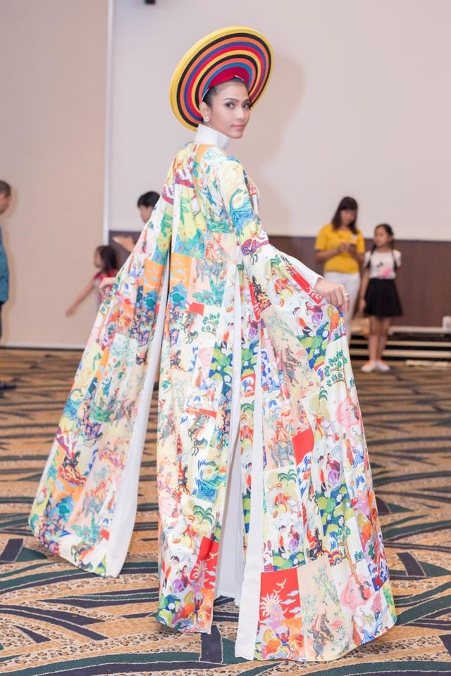 Điểm nhấn trong bộ trang phục của Trương Thị May chính là áo choàng được trang hoàng màu sắc bắt mắt, mang hơi hướng tuổi thơ, bên trong là bộ áo dài trắng tinh khôi, đúng như phong cách đơn sắc mà Trương Thị May yêu thích.