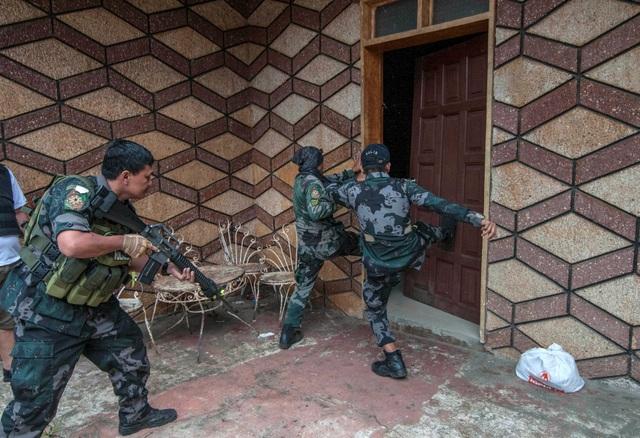 """Ông Eduardo Ano cho biết các phiến quân đã tích trữ lương thực cũng như vũ khí trong các nhà thờ, trường học, các vị trí dân sự cũng như mạng lưới đường hầm dưới lòng đất để chuẩn bị cho một cuộc chiến """"dài hơi"""" với quân đội chính phủ. Trong ảnh: Các binh lính và cảnh sát Philippines đạp cửa xông vào một ngôi nhà để truy lùng các phiến quân ẩn náu. (Ảnh: Reuters)"""