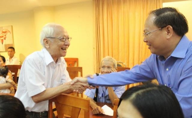 Ông Tất Thành Cang (phải) tại buổi lễ chăm lo tết cho người dân nghèo. Ảnh PLO
