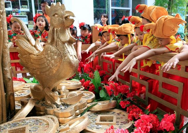 Những em nhỏ mang hai dòng máu Philippines và Trung Quốc, đầu đội mũ hình con gà, tung một đồng xu trước tượng cây Thần tài, với hy vọng mang lại nhiều may mắn trong năm mới 2017. (Ảnh: Reuters)