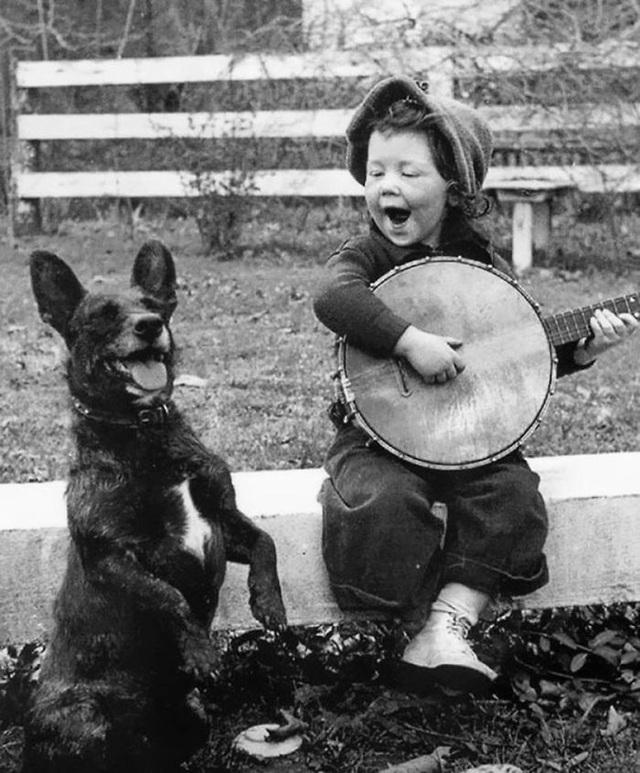 Cô bé đàn hát bên chú chó cưng.