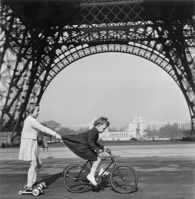 Trẻ nhỏ chơi bên chân tháp Eiffel. (Ảnh: Robert Doisneau)