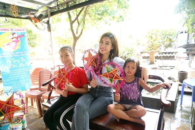 Hoa hậu Việt Nam Đỗ Mỹ Linh tươi cười vui chơi với em nhỏ làng chài