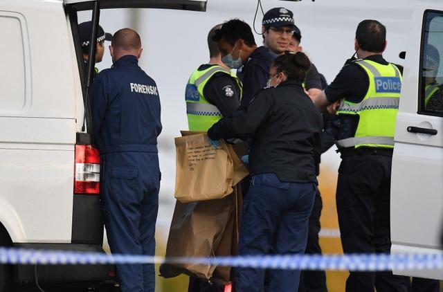 Cảnh sát cầm túi chứa các bằng chứng của vụ tấn công (Ảnh: Reuters)