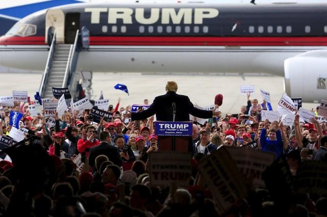 """Cùng với đội ngũ tranh cử tận tâm và nhiệt huyết của mình, tỷ phú Trump đã ngồi trên chuyên cơ Trump để đi tới khắp các bang của nước Mỹ, kêu gọi các cử tri ủng hộ ông trong cuộc đua vào Nhà Trắng. Cùng với khẩu hiệu """"Đưa nước Mỹ vĩ đại trở lại"""", ứng viên đảng Cộng hòa cam kết vực dậy nền kinh tế Mỹ, đưa việc làm trở về tay người Mỹ, bảo vệ nước Mỹ trước nguy cơ khủng bố cùng nhiều lời hứa khác nếu ông được bầu làm tổng thống. (Ảnh: Getty)"""