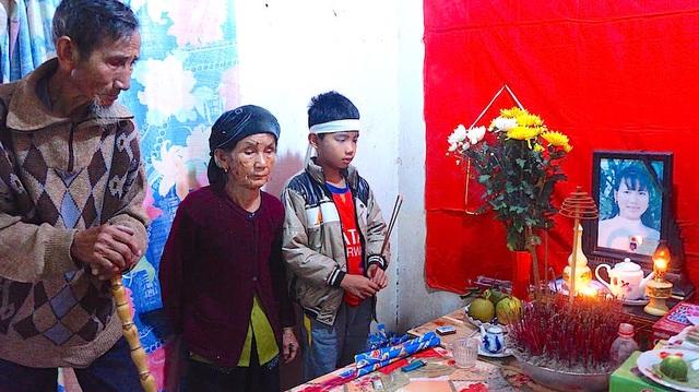 Thụ và ông bà ngoại trước bàn thờ mẹ.