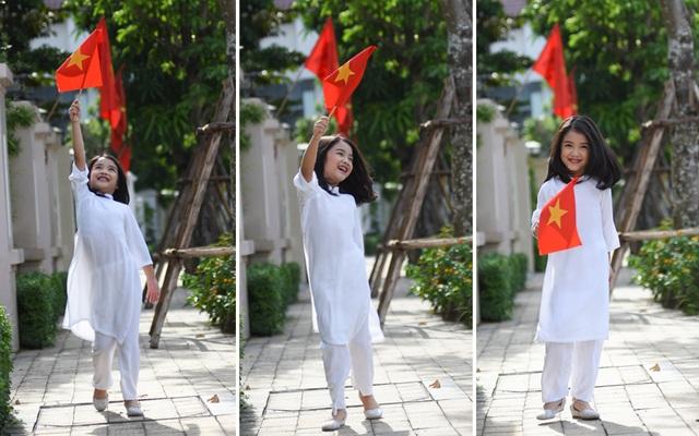 Bảo Hân diện áo dài trắng, nở nụ cười hồn nhiên khi ngắm những lá cờ đỏ sao vàng tung bay trên phố.