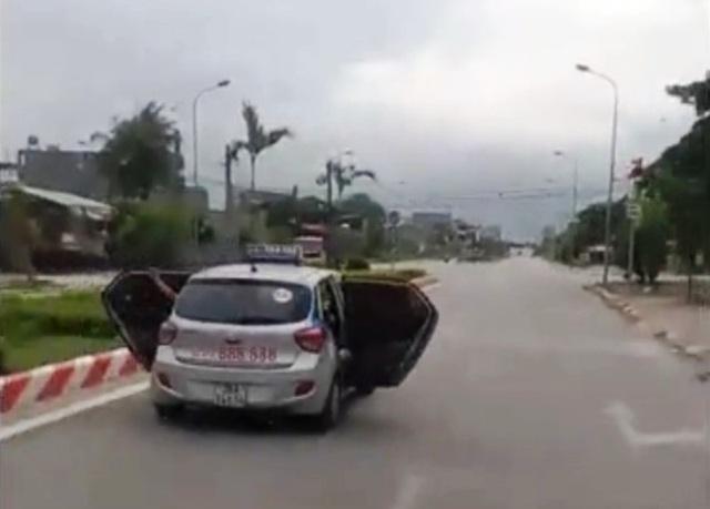 Chiếc xe taxi vừa chạy vừa mở 2 cửa sau (Ảnh: Cắt từ video)