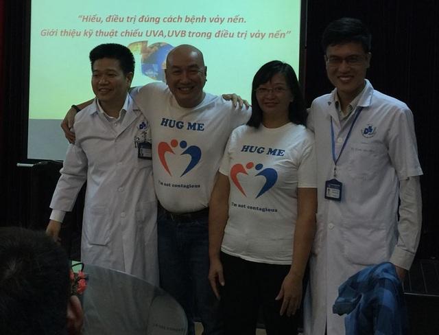 PGS. TS. Lê Hữu Doanh (ngoài cùng bên trái) và BS Hoàng Văn Tâm (ngoài cùng bên phải) hưởng ứng thông điệp Hug me (Hãy ôm tôi) cùng anh Trần Hồng Trường và thành viên Hội bệnh nhân vảy nến (Ảnh: T.P)