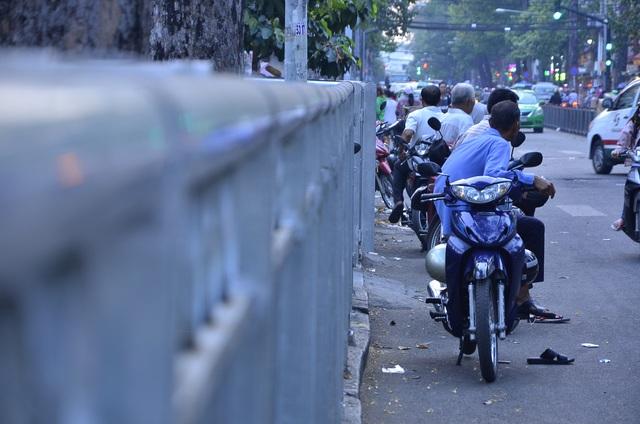 Sau khi vỉa hè bị rào chắn, nhiều người chạy xe ôm phải tràn xuống lòng đường để ngồi chờ khách.