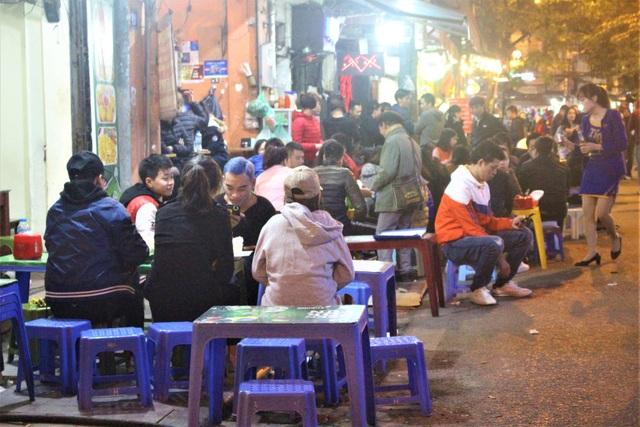 Một dãy những quán nhậu đêm đông khách tới nỗi ngồi tràn ra cả lòng đường. (Ảnh: Hồng Vân)