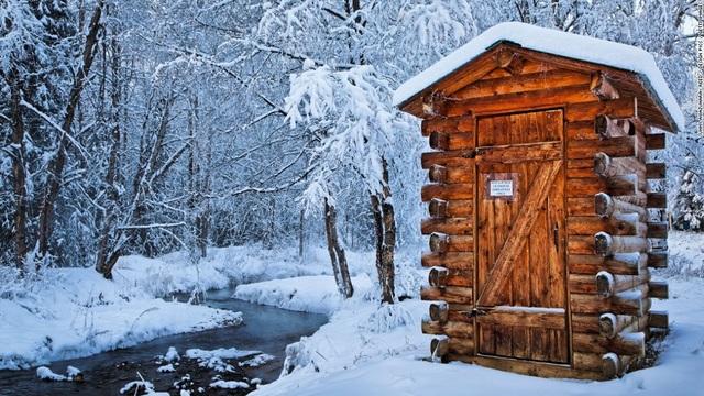 Nhà vệ sinh làm bằng gỗ nằm tại khu nghỉ dưỡng suối nước nóng Chena ở Alaska, Mỹ. Màu gỗ trầm tạo nên sự ấm áp giữa màn tuyết trắng xóa.