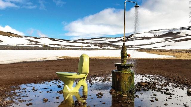 Thêm một nhà vệ sinh công cộng nằm giữa thiên nhiên ở Krafla, Iceland. Bên cạnh WC là một vòi tắm sen đã cũ.