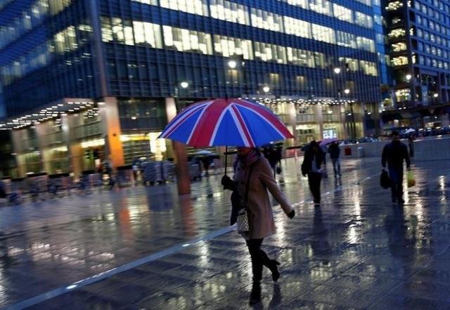 Công nhân đi bộ trong mưa tại trung tâm thương mại tài chính Canary Wharf, London. (Nguồn: Eddie Keogh)