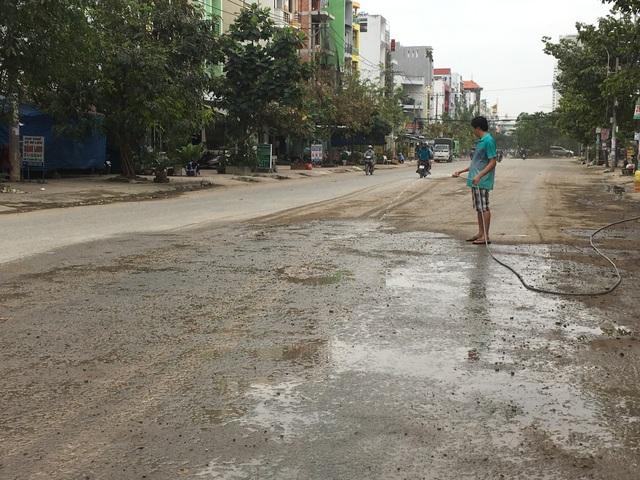 Người dân phải xịt nước để giảm bụi sau khi xe ben chạy qua