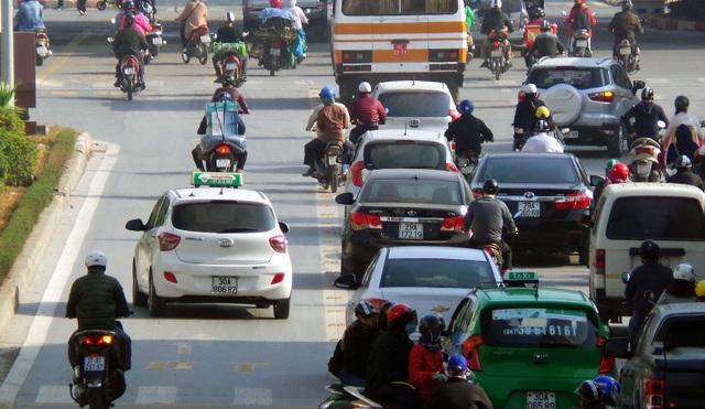 Vượt qua đèn đỏ, một số ô tô, xe máy nhanh chóng nhập làn xe buýt nhanh.
