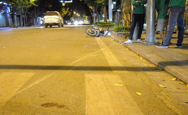 Chiếc xe máy bị xe cấp cứu húc văng ra xa.
