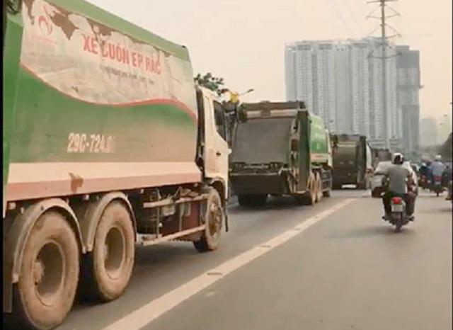4 xe chở rác nối đuôi nhau di chuyển vào làn xe buýt nhanh BRT. (Ảnh cắt từ clip).