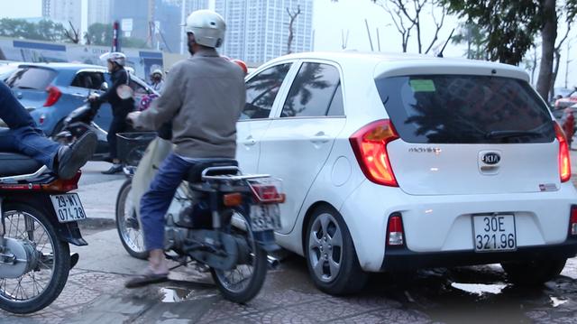 Không chỉ có xe máy, nhiều ô tô cũng coi vỉa hè như đường để đi. Chiếc ô tô này chạy dọc vỉa hè phố Lê Văn Lương sau đó rẽ ngang để sang đường.