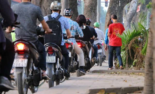 Hình ảnh dòng xe máy tràn lên vỉa hè, giành hết không gian của người đi bộ.
