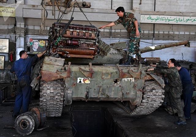"""Theo Sputnik, mặc dù chiến sự vẫn đang diễn ra ác liệt tại nhiều khu vực ở Syria nhưng tại những khu vực do chính phủ kiểm soát, sự tồn tại của những nhà máy công nghiệp chưa bị chiến tranh tàn phá đã giúp chính quyền Damascus tiếp tục nuôi hy vọng về việc """"tái sinh"""" sức mạnh chiến đấu. Trong ảnh: Các công nhân đang lắp đặt một động cơ mới vào một xe tăng quân sự tại nhà máy sửa chữa xe tăng và xe bọc thép ở Damascus."""
