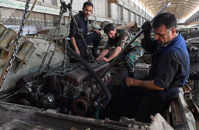 Các công nhân lắp đặt một động cơ mới vào một xe bọc thép.