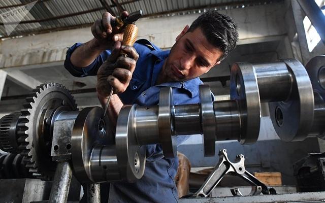 Một công nhân đang miệt mài làm việc bên trong một nhà máy sửa chữa xe tăng ở thủ đô của Syria.