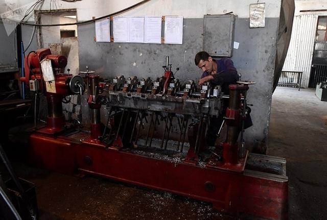 Công nhân đang làm việc bên trong một nhà máy sửa chữa xe bọc thép ở Damascus.