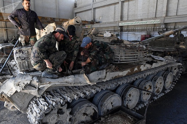 Một nhóm công nhân cùng nhau tháo lắp và sửa chữa một xe tăng bị hư hỏng nặng.