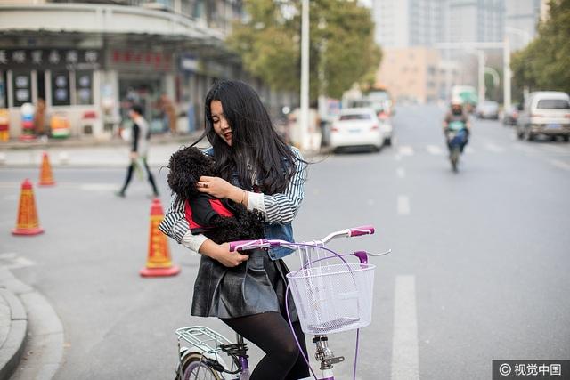 """Mỗi lần khi có khách muốn đến xem căn hộ trước khi thuê nửa giường, Xiao Ying và chú chó cưng HeiHei lại ra đường đón khách hàng tiềm năng. Trải nghiệm sống ở nước ngoài một mình khiến Xiao Ying trông chững chạc so với tuổi. """"Tôi tin vào sự tử tế giữa những người lạ"""", cô giải thích. (Ảnh: VCG)"""