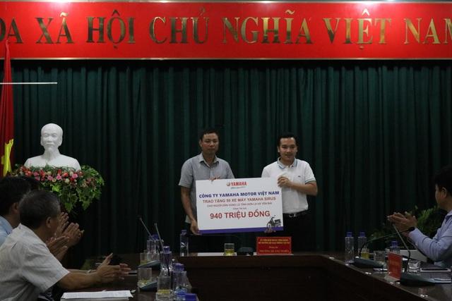 Ông Đậu Quang Huy (đứng bên phải) trao 50 xe máy Yamaha Sirius cho người dân vùng lũ