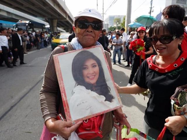 Người ủng hộ mang theo ảnh của bà Yingluck để ủng hộ bà trước phiên tòa (Ảnh: Reuters)