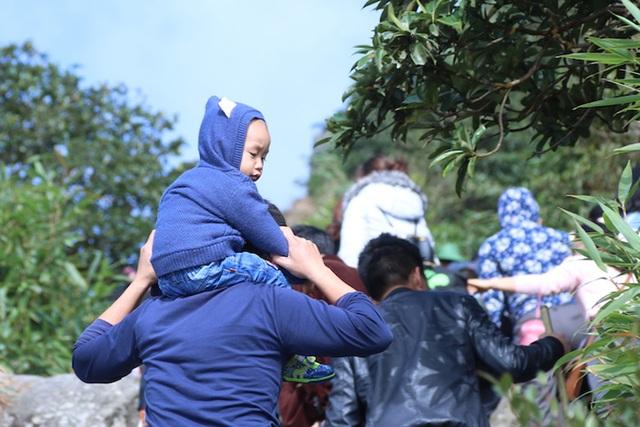 Một cháu nhỏ được bố kiệu trên vai trong suốt quá trình đi bộ leo lên đỉnh Yên Tử.