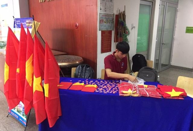 Sinh viên trường ĐH Nguyễn Tất Thành với cờ, áo và sticker cờ đỏ sao vàng chuẩn bị sẵn để sinh viên cổ động