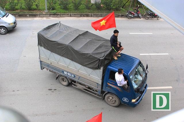 Một người đàn ông ngồi lên nóc chiếc xe tải, quay đầu ngay giữa đường Võ Chí Công.