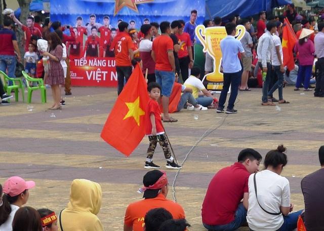 Một nhóc tì... cầm cờ đỏ sao vàng chạy tung tăng trong sân...