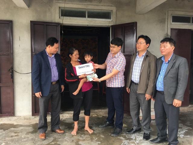 Phóng viên Dân trí cùng đại diện chính quyền địa phương trao quà bạn đọc cho gia đình cháu Thanh Bình