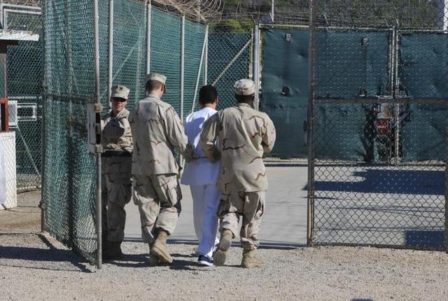 """Cựu Bộ trưởng Quốc phòng Mỹ Donald Rumsfeld cho biết nhà tù Guantanamo được mở cửa với mục đích giam giữ và thẩm vấn những """"đối tượng đặc biệt nguy hiểm"""" và để hành quyết các tội phạm chiến tranh. Trong ảnh: Các binh sĩ Hải quân Mỹ áp giải một nghi phạm vào trại Delta năm 2008."""