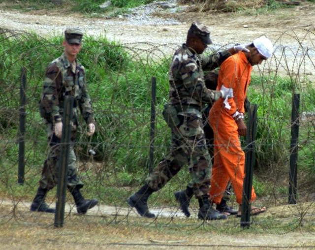 Mỹ từng tuyên bố nhà tù Guantanamo không thuộc lãnh thổ Mỹ nên không bắt buộc áp dụng hiến pháp Mỹ. Tuy nhiên, Guantanamo không do Cuba quản lý nên trên thực tế nhà tù này cũng không thể áp dụng luật pháp Cuba. Do vậy, bản chất pháp lý của Guantanamo cho đến nay vẫn là vấn đề để ngỏ. Trong ảnh: Phạm nhân Trại X-Ray được đưa tới phòng thẩm vấn năm 2002.