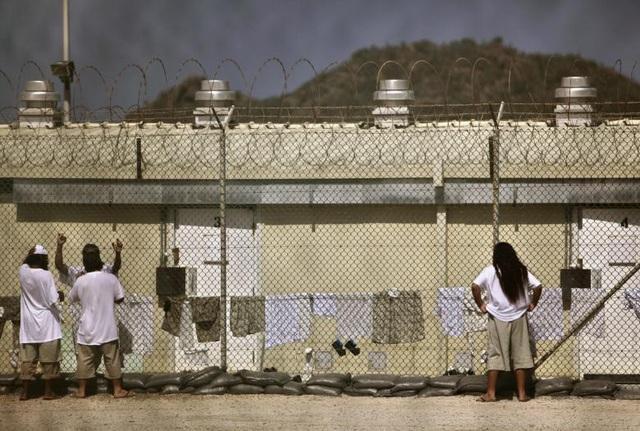 Ngay sau khi nhậm chức năm 2009, cựu Tổng thống Obama đã ký sắc lệnh hành pháp để đóng cửa các trại giam ở nhà tù Guantanamo trong vòng một năm. Tuy nhiên Quốc hội Mỹ không đồng tình và chỉ chấp thuận giảm số lượng phạm nhân từ 234 xuống còn 40 người. Trong ảnh: Các phạm nhân nói chuyện qua hàng rào ở Trại 4.