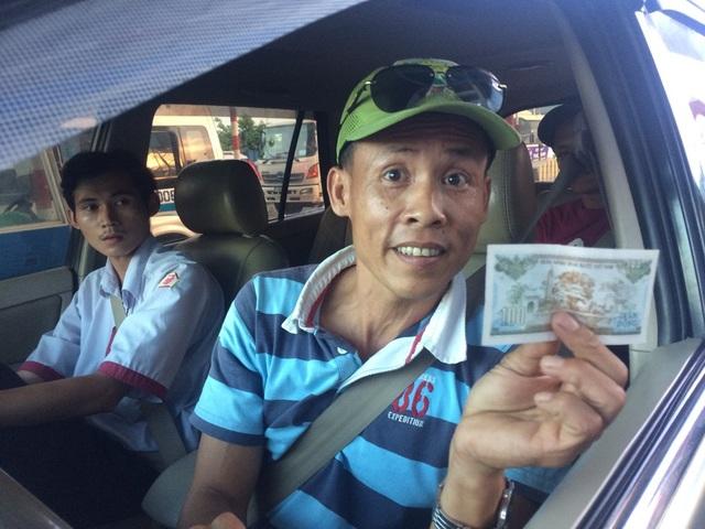 Tài xế này vui mừng nhận lại tờ tiền 100 đồng từ nhân viên thu phí