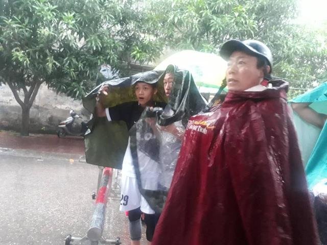 Nhiều người dân vẫn đội mưa theo dõi vụ việc từ xa.