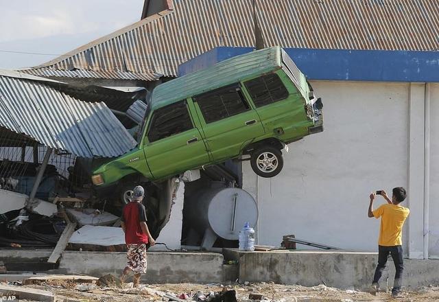 Xe ô tô bị cuốn lên nóc nhà sau động đất. (Ảnh: AP)