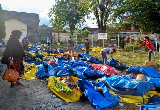 Gia đình các nạn nhân thiệt mạng trong thảm họa kép tại Indonesia nhận diện người thân tại nơi tập kết các thi thể. (Ảnh: EPA)